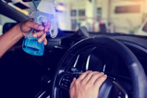 a man is disinfecting his car with a hand spray - Nola Automotive